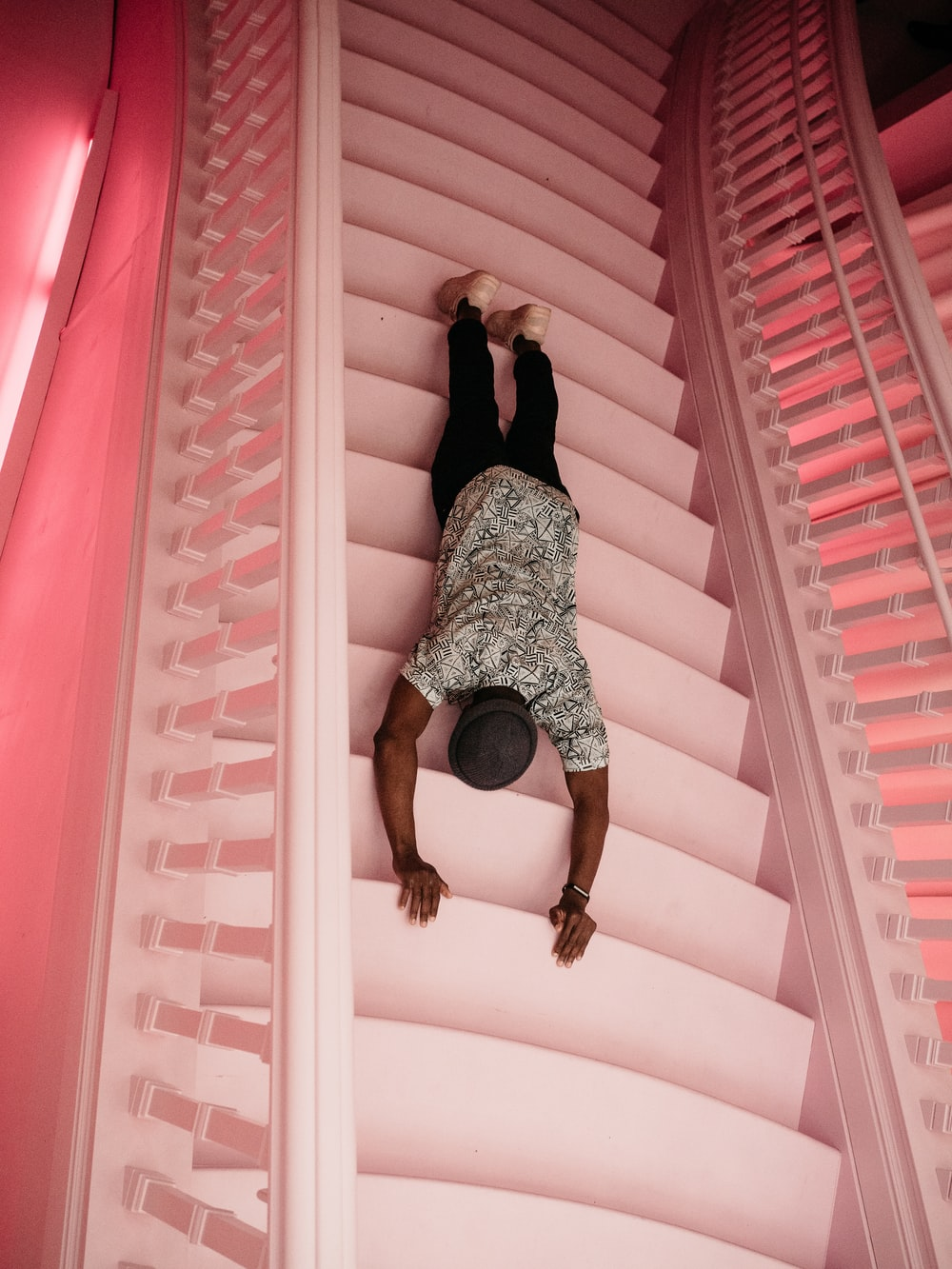 man wearing black and white crew-neck shirt and black pants laying on pink concrete stairs
