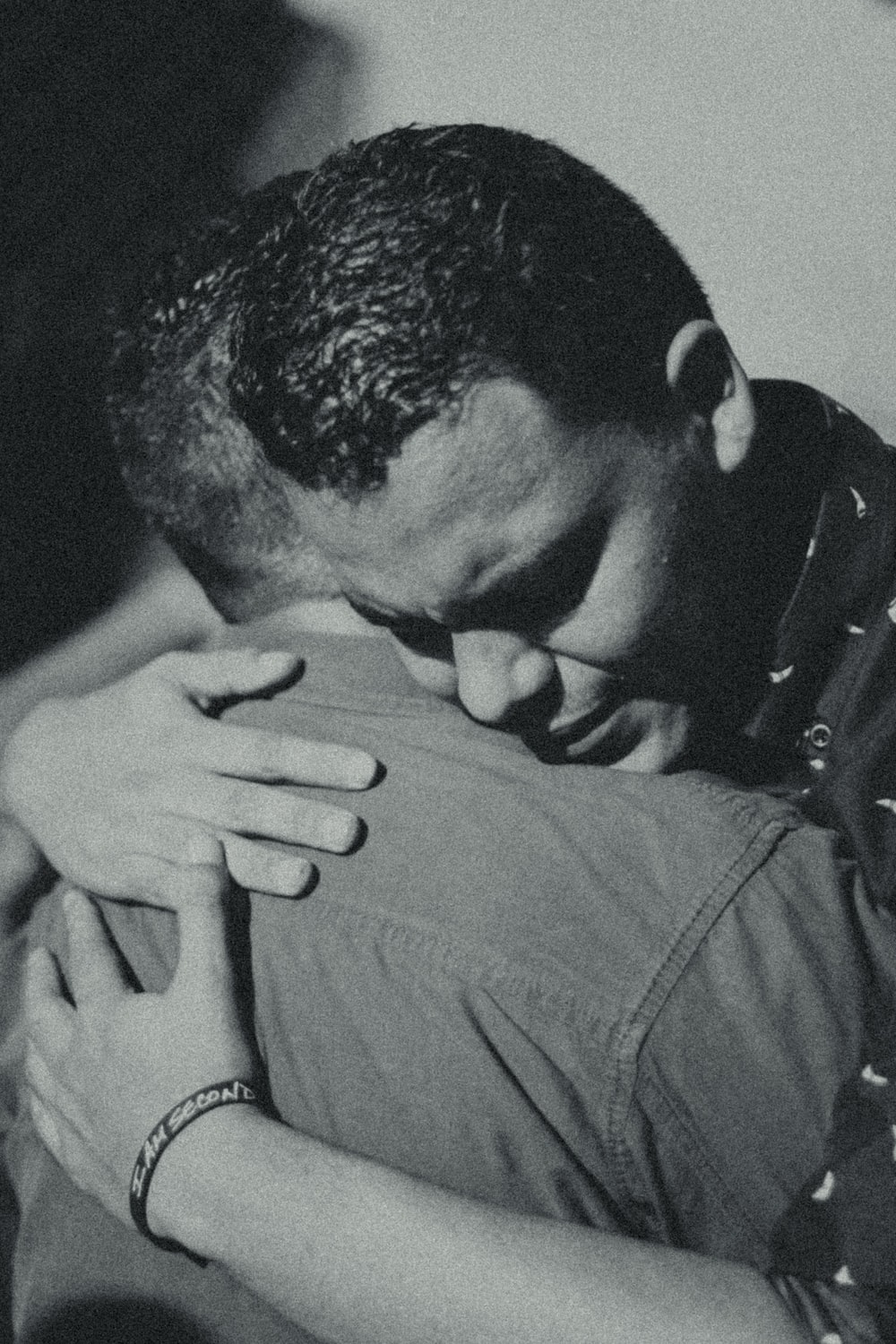 grayscale photography of two men hugging