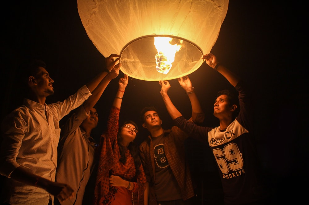 woman and men holding on a paper lantern