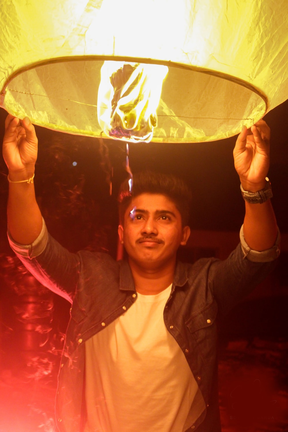 man holding on a lighted paper lantern