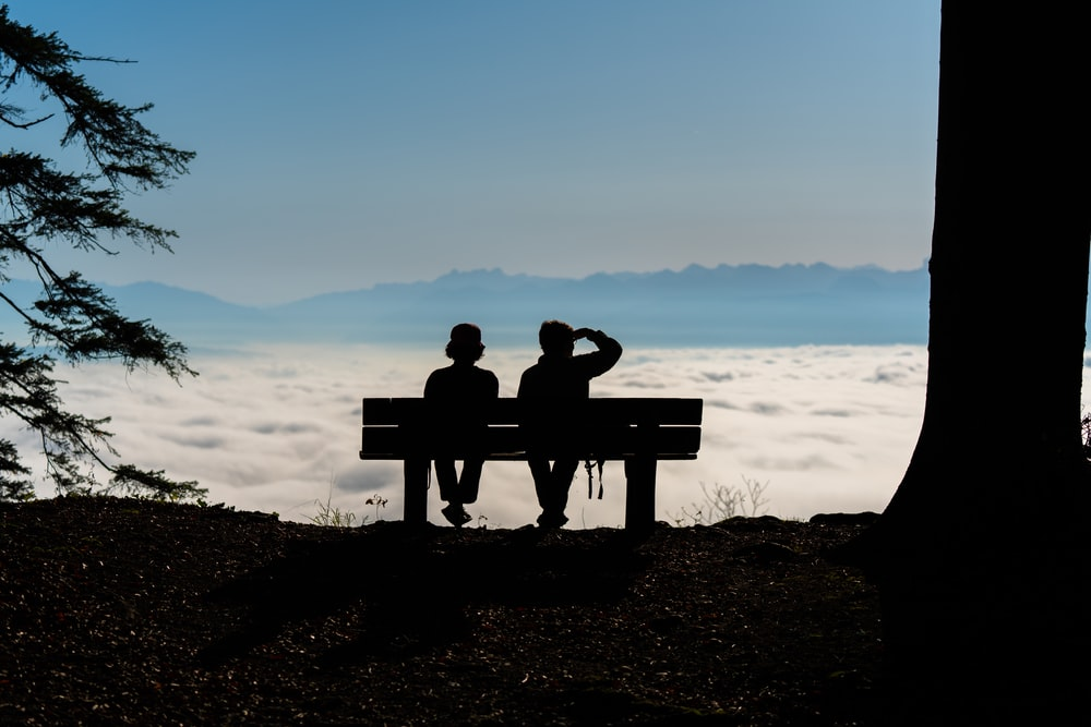 two persons sitting on a bench overlooking a sea of clouds