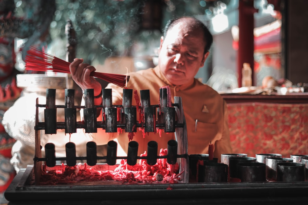 shallow focus photo of man holding incense