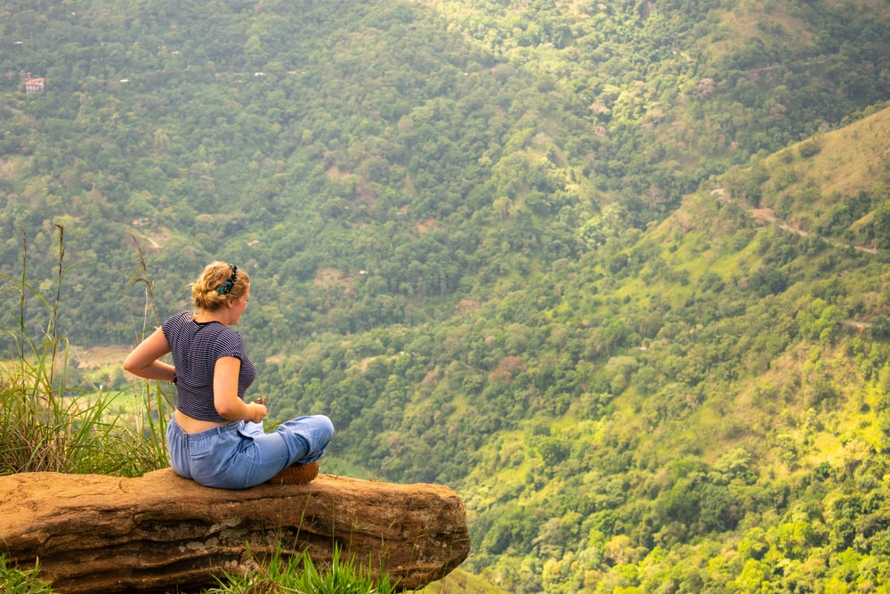 woman sitting on cliff in forest