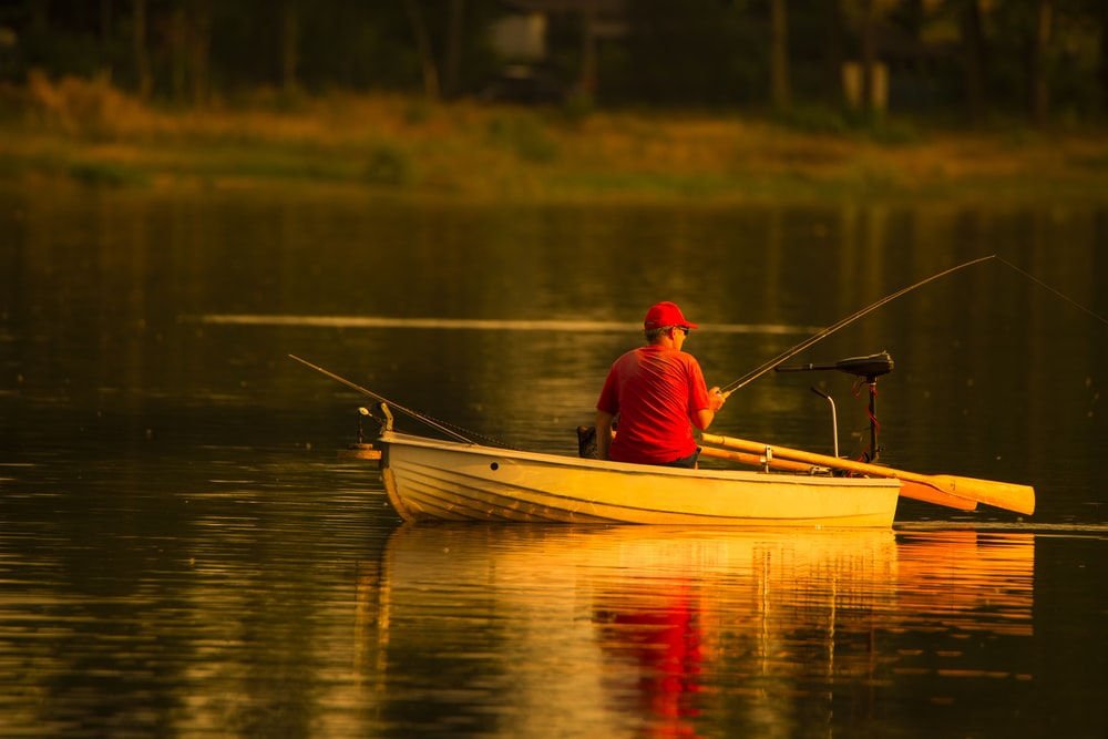 man in red cap and shirt fishing in lake