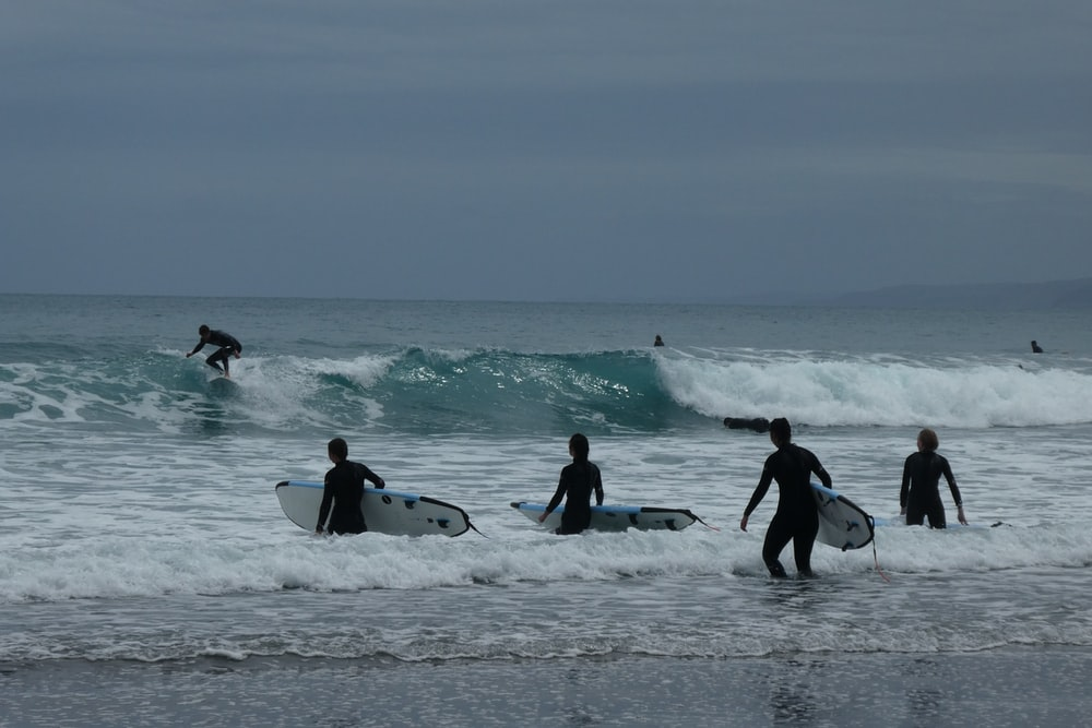 five person playing surfing