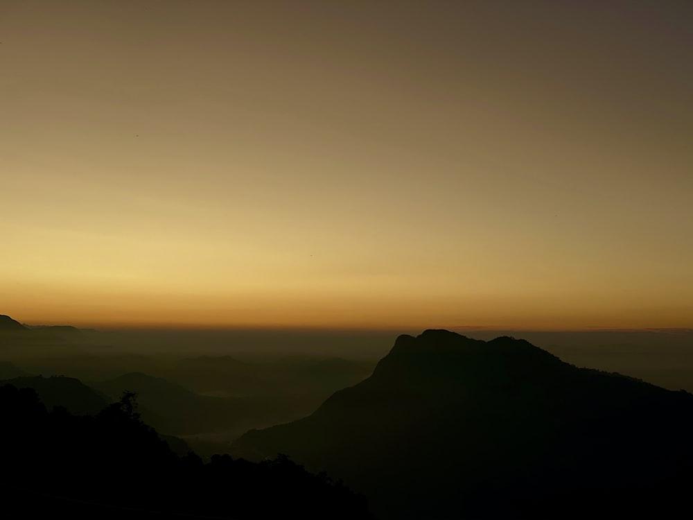 golden hour under brown mountain ranges