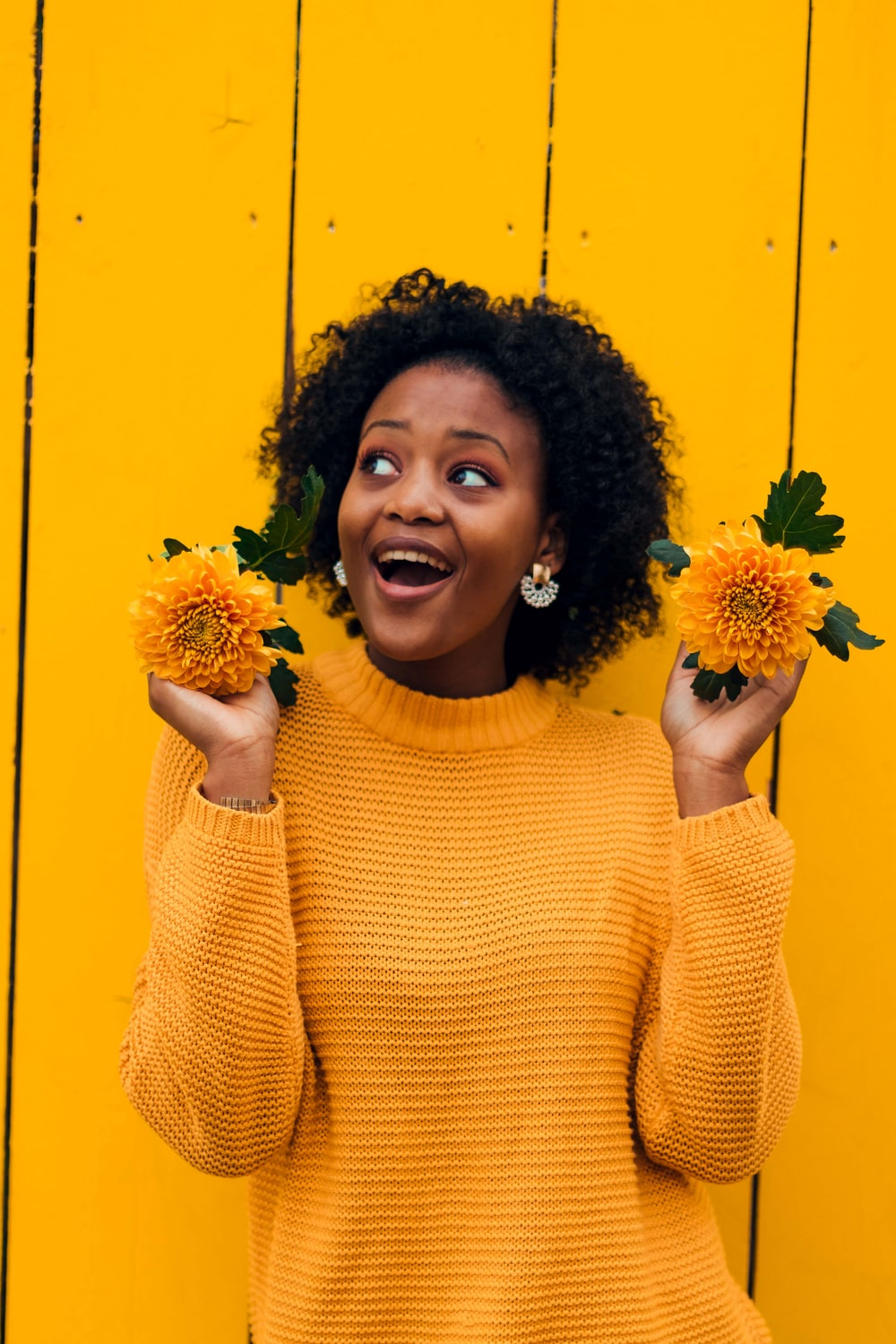 woman standing beside yellow wall while holding yellow flowers