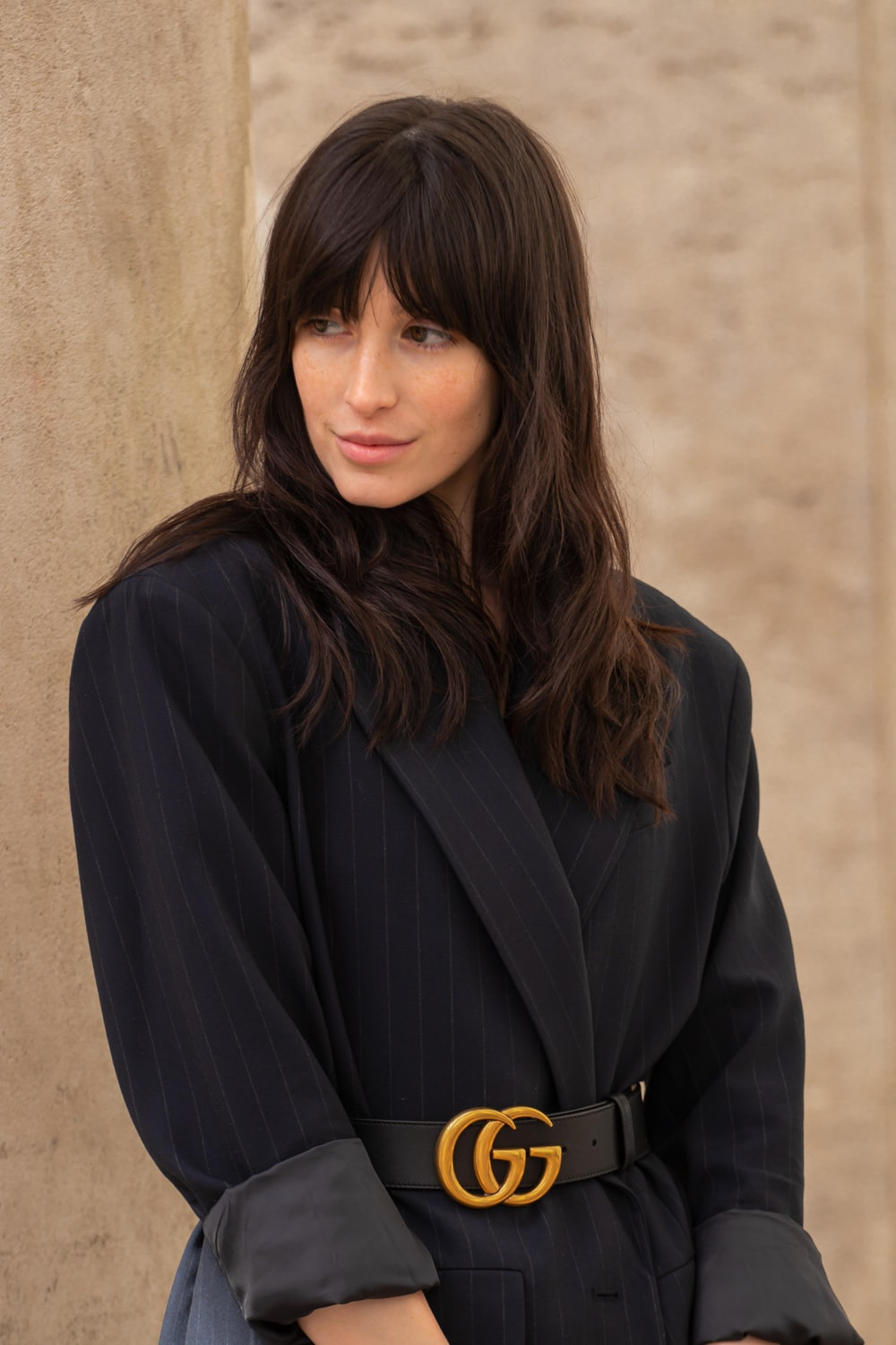 woman in black coat and black Gucci belt