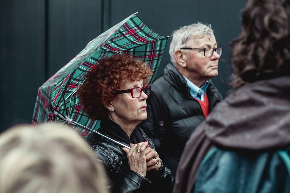 man and woman under green umbrella