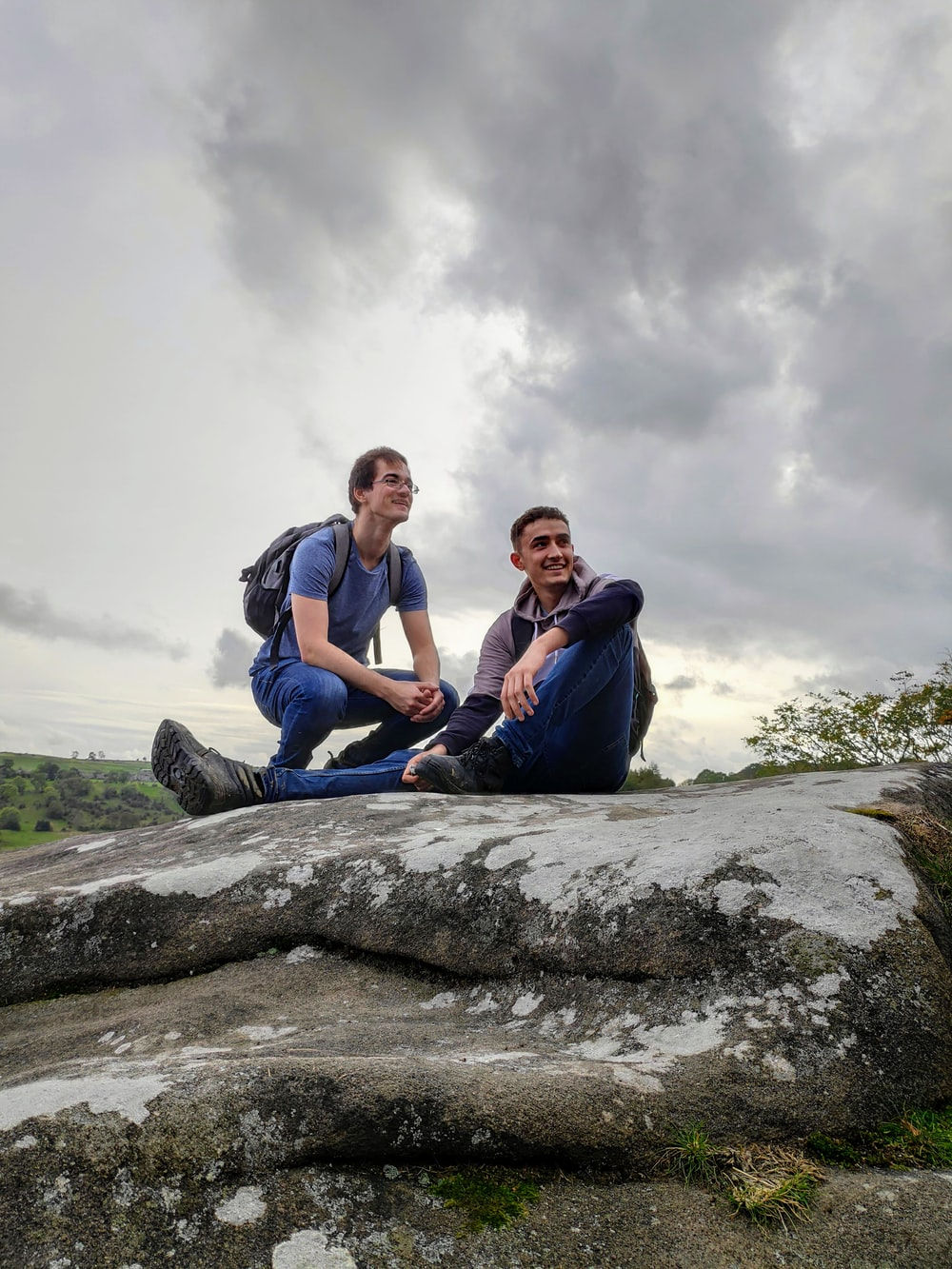 two men sitting on gray rock