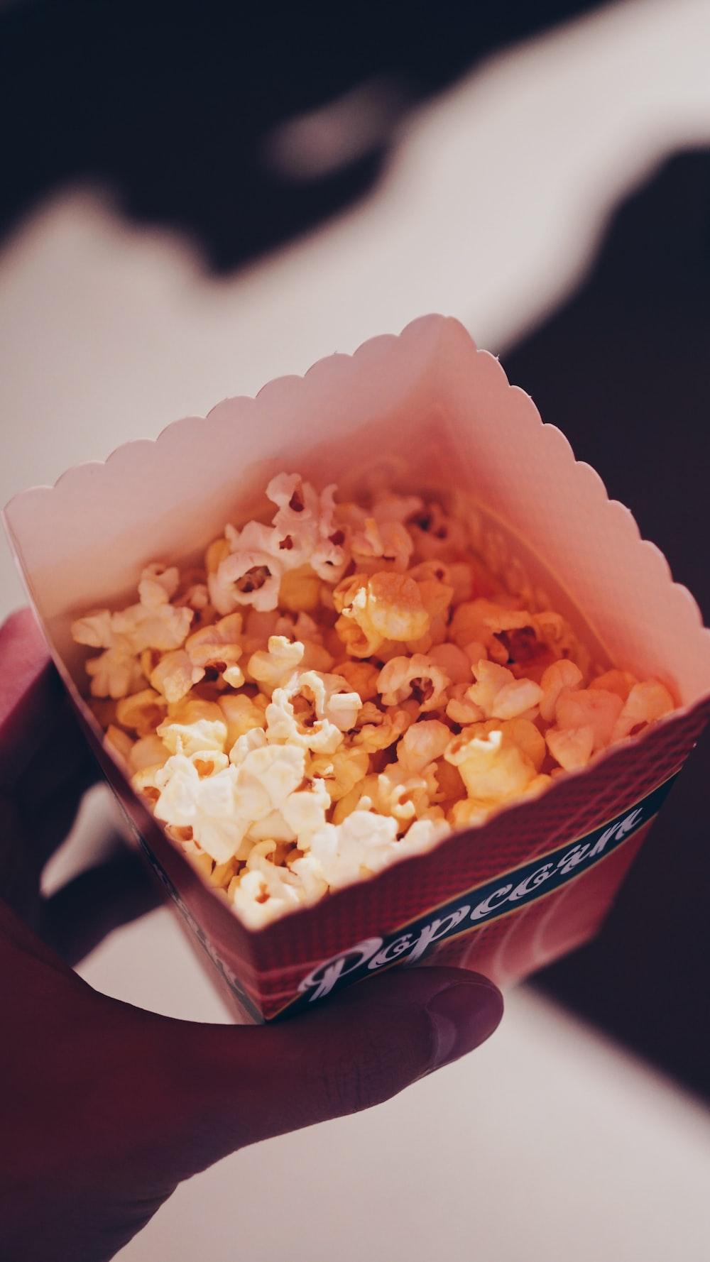 person holding popcorn in box