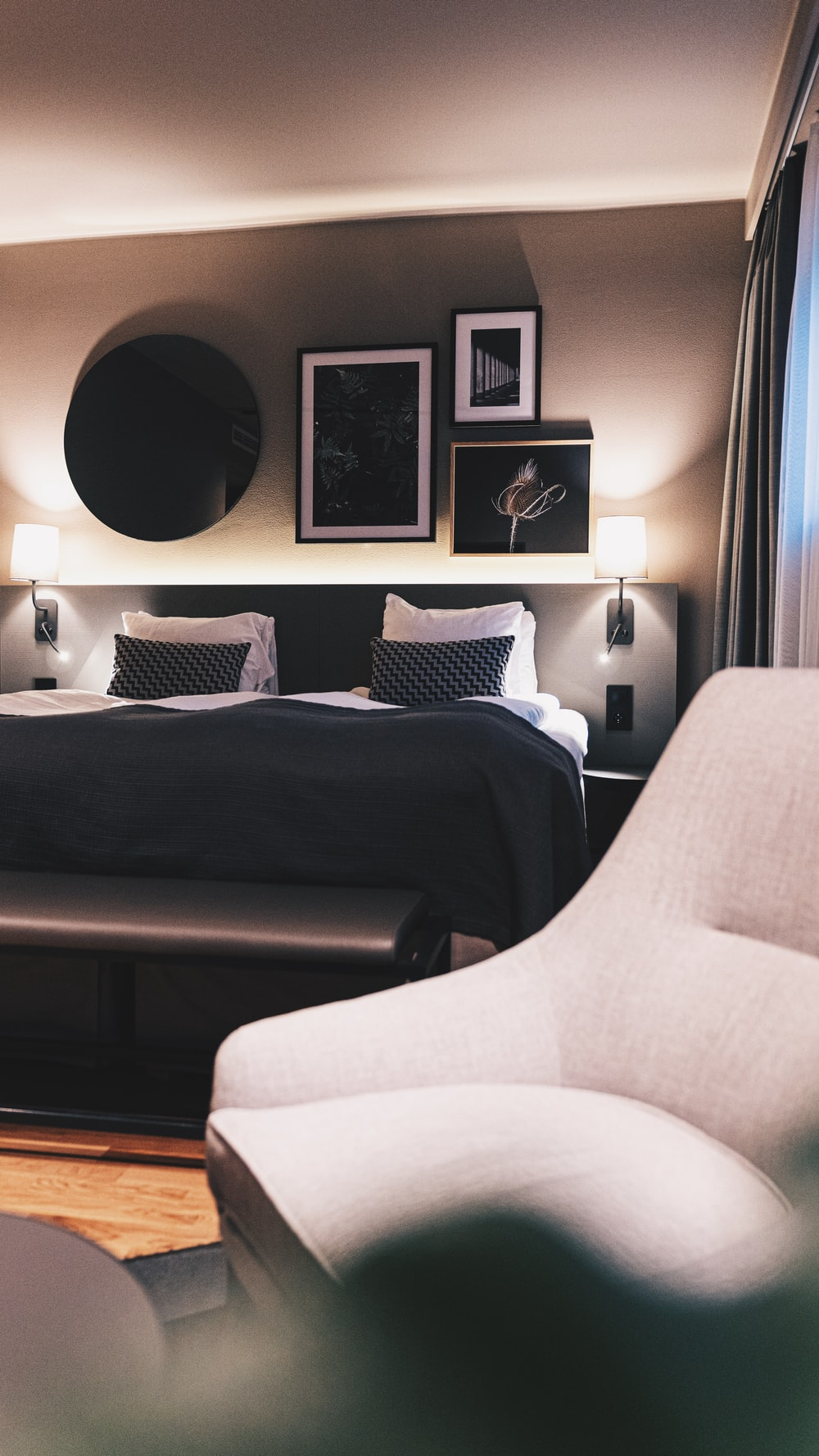 white sofa chair beside black sofa