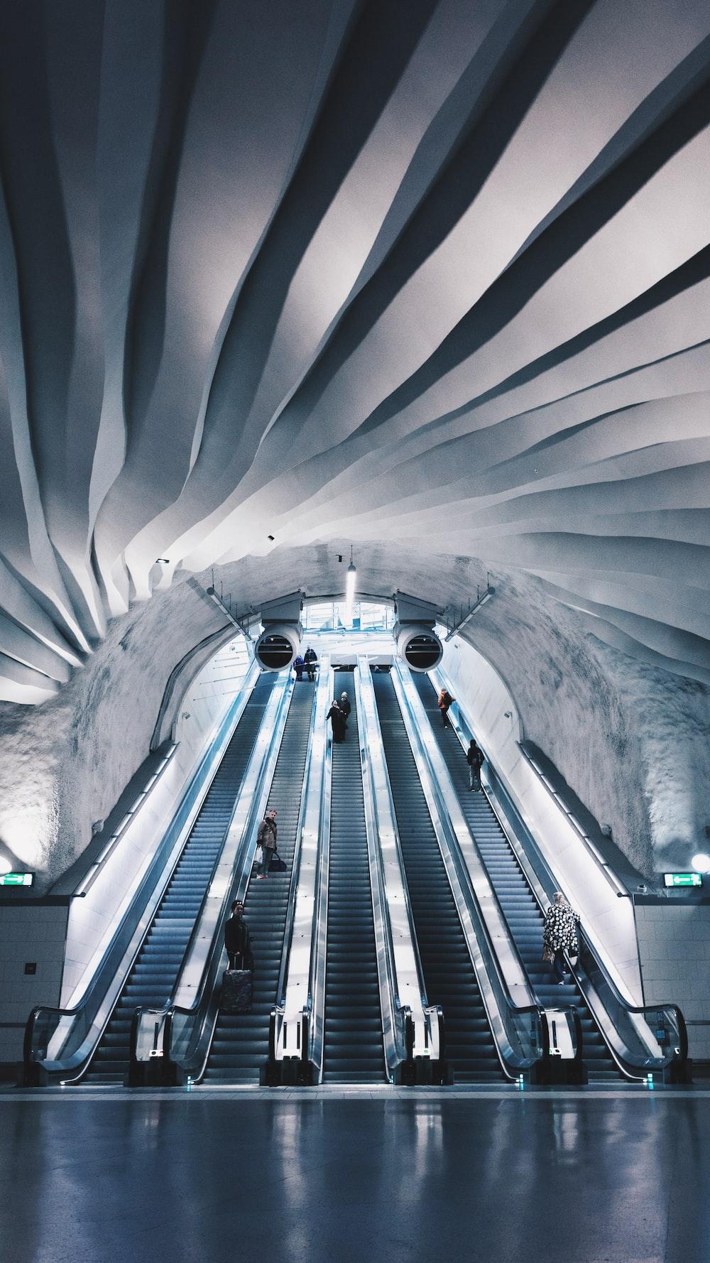 people walk on escalator inside building