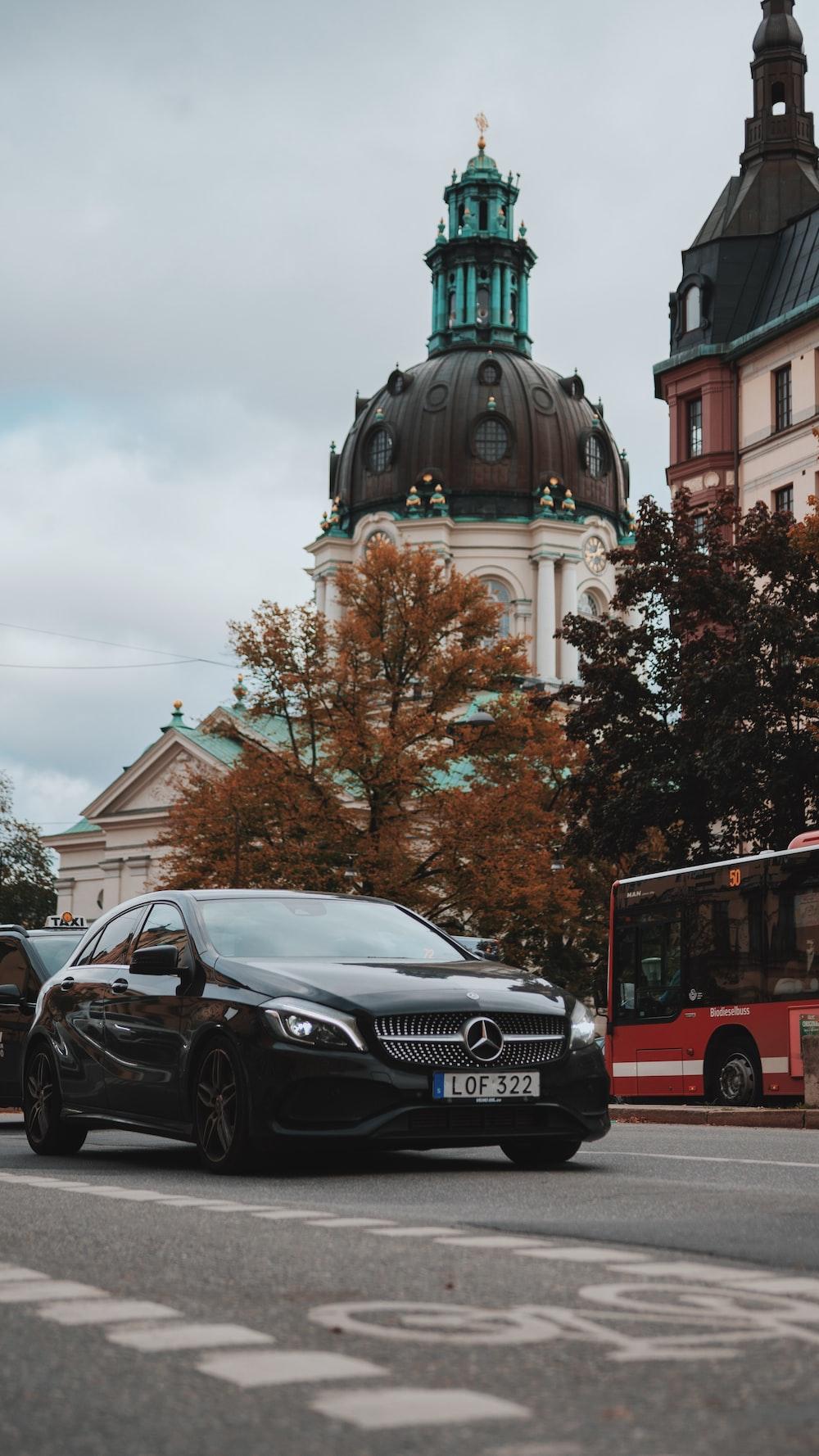 black Mercedes-Benz sedan in the road
