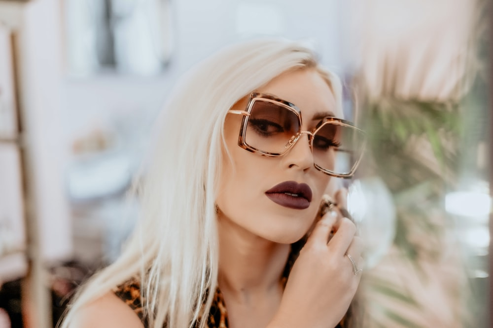 woman wears dark brown matte lipstick and oversized sunglasses