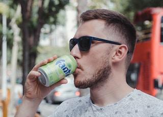man drinking fanta soda can