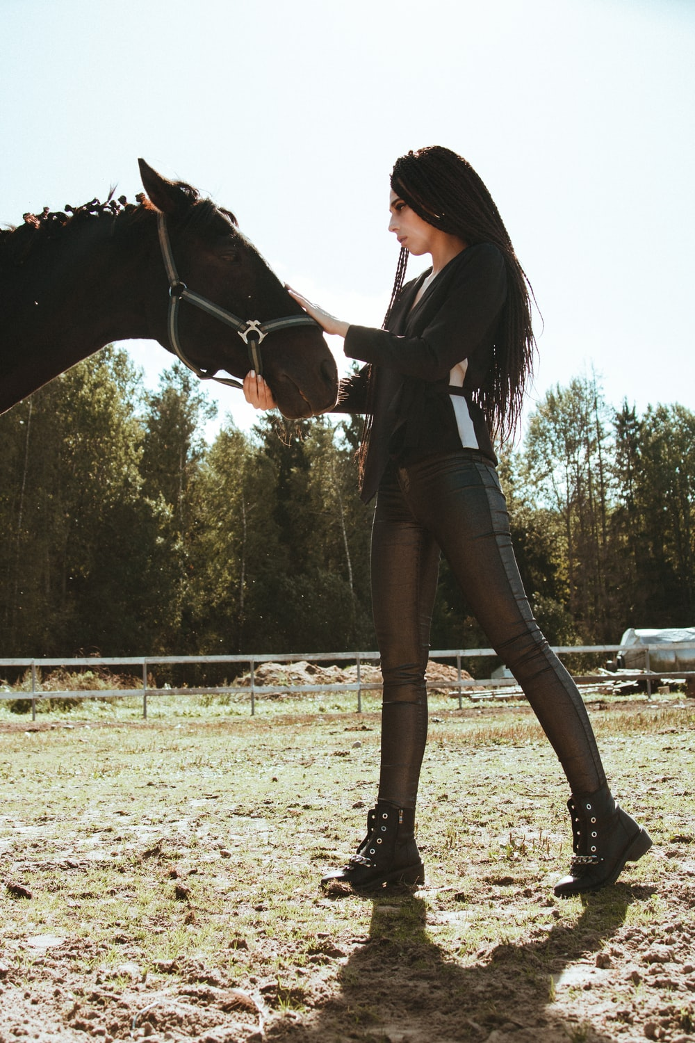 woman wearing black long-sleeved blouse standing and touching black horse on green field during daytime