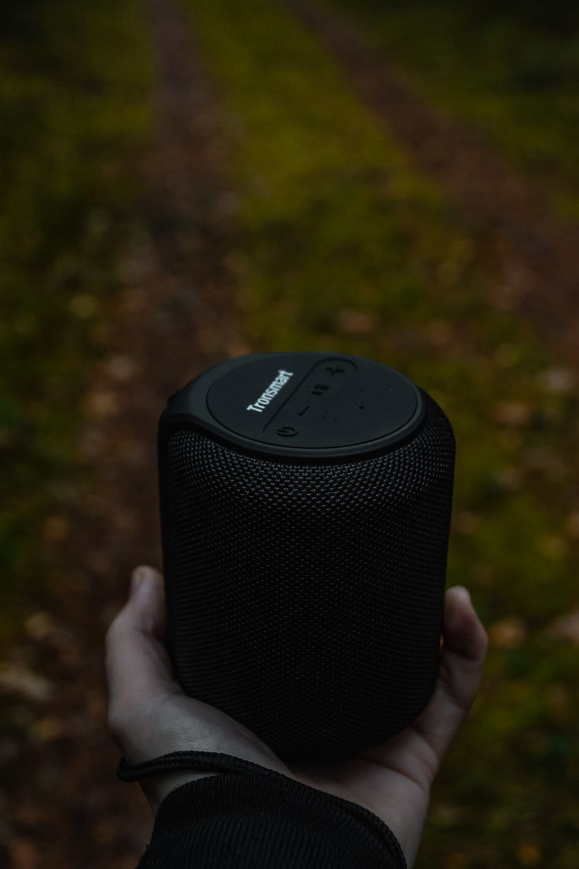 person holding black wireless speaker