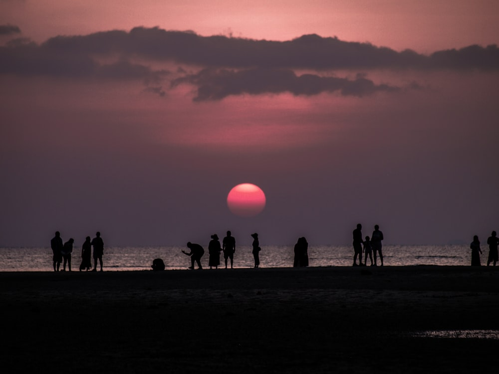 people standing near seashore showing full moon during night time