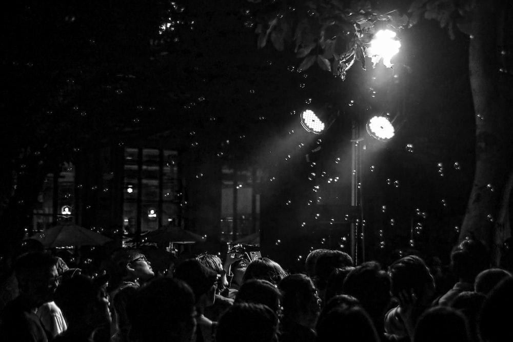 greyscale photography of people beside tree