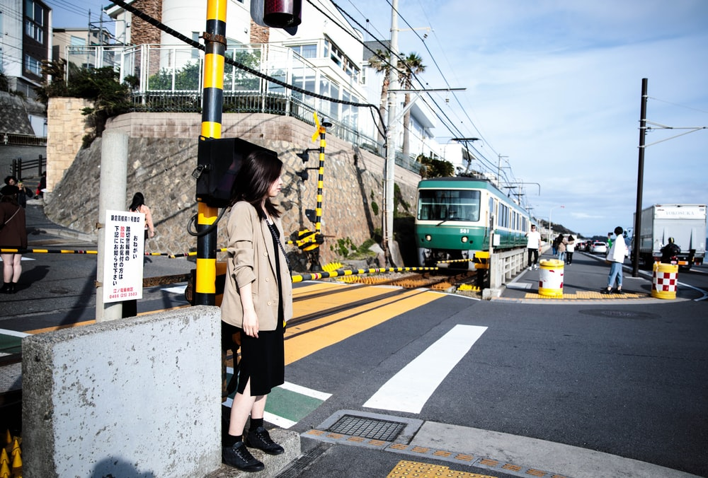 woman standing near road viewing train and buildings under white and blue sky during daytime