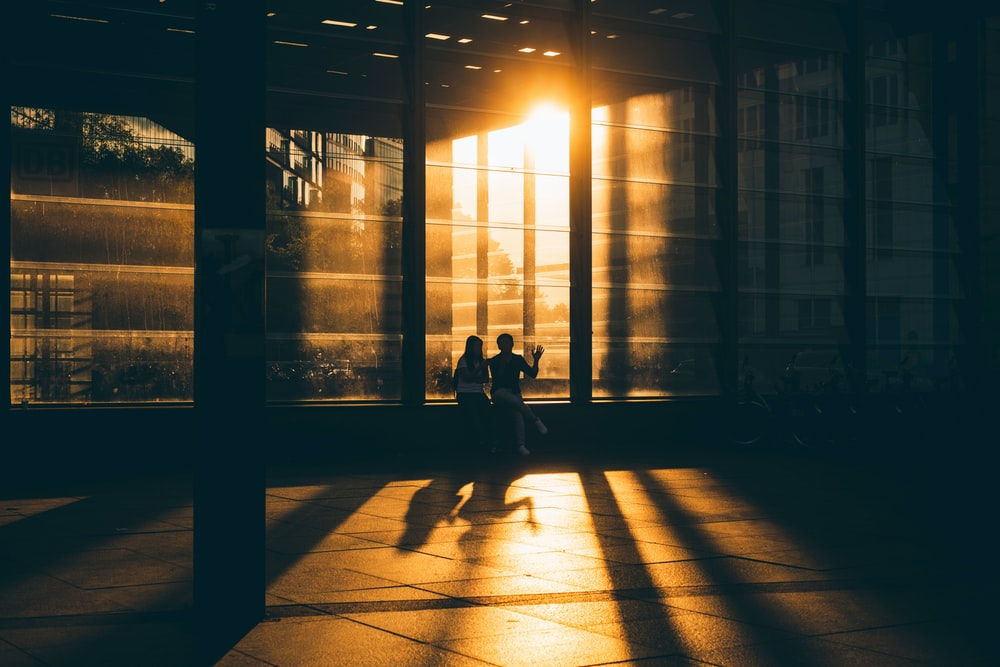 two person standing near glass building during night time