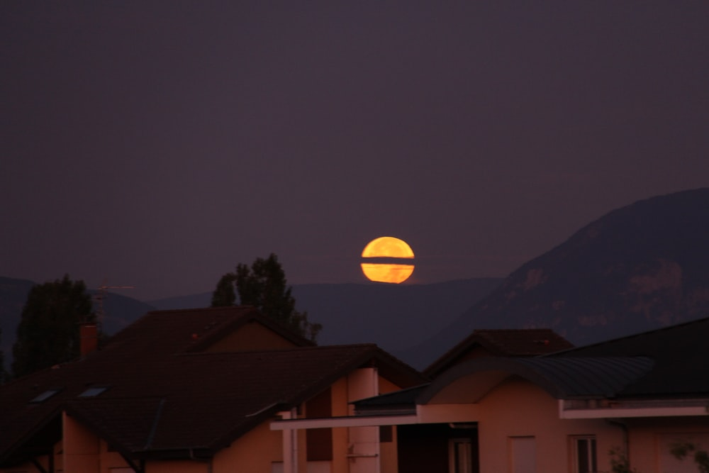 houses viewing mountain and full moon during night time