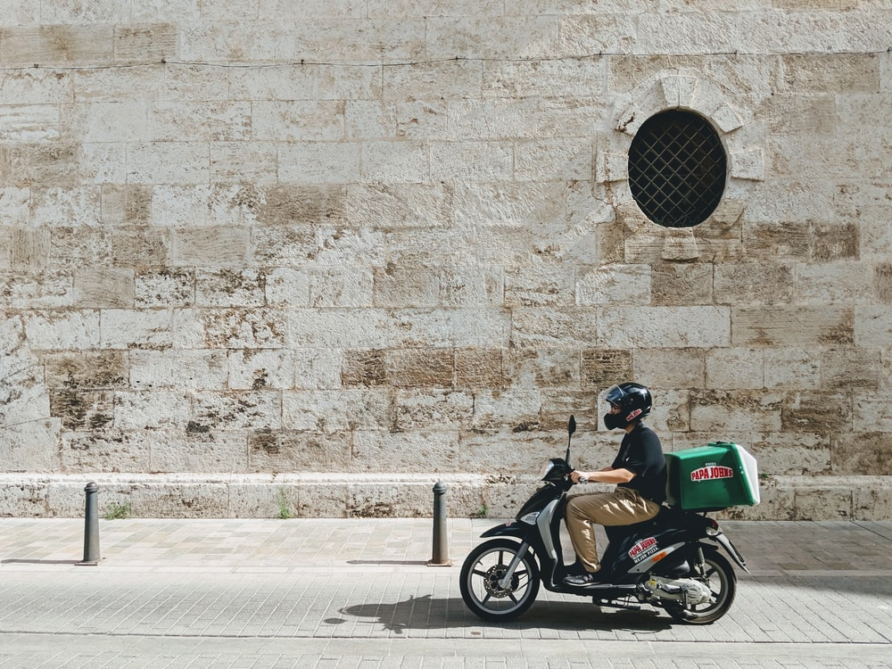 良い配達モータースクーターを運転する男