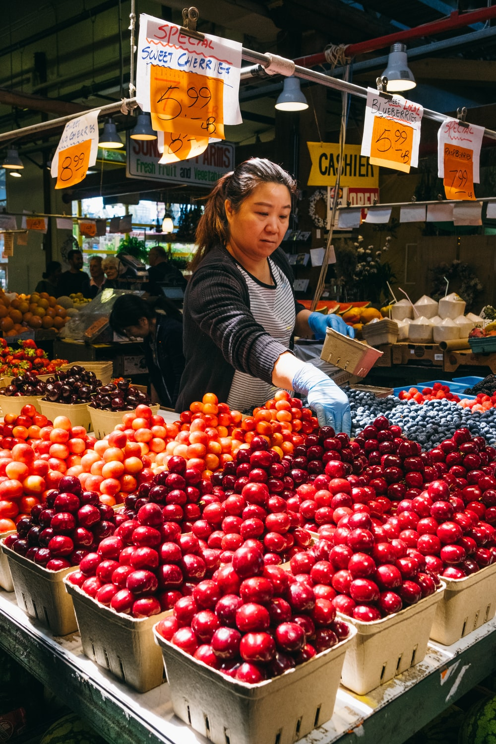 woman standing in front of variety of fruits