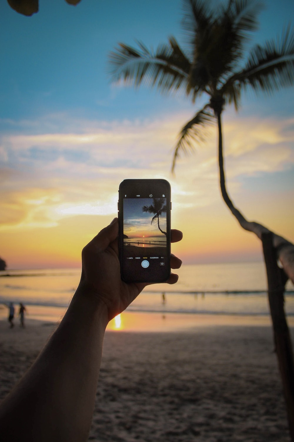 person holding smartphone displaying camera with body of water during golden hour