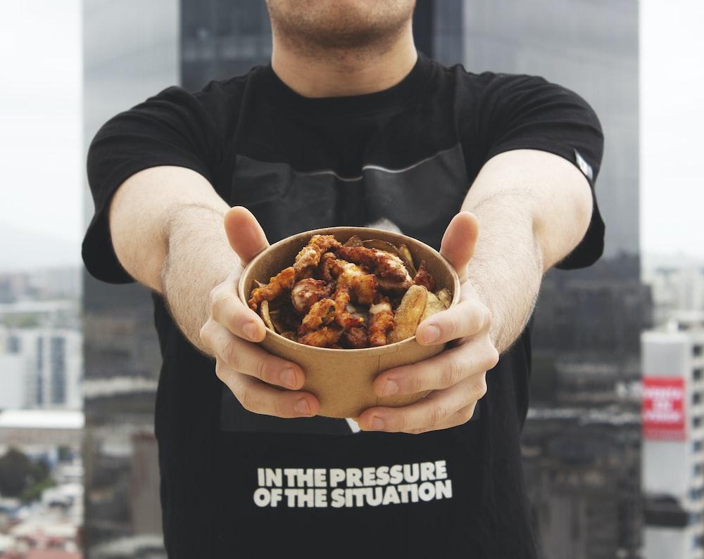 man holding bowl of food