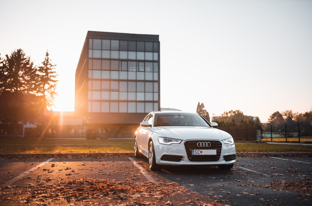 white Audi sedan parked on concrete parking area surrounded by dried leaves