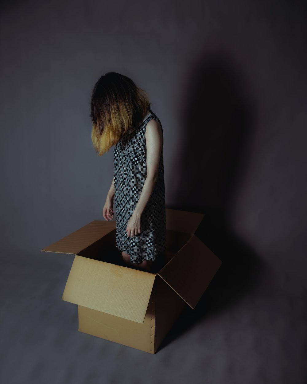 girl wearing gray and white sleeveless dress standing on cardboard box
