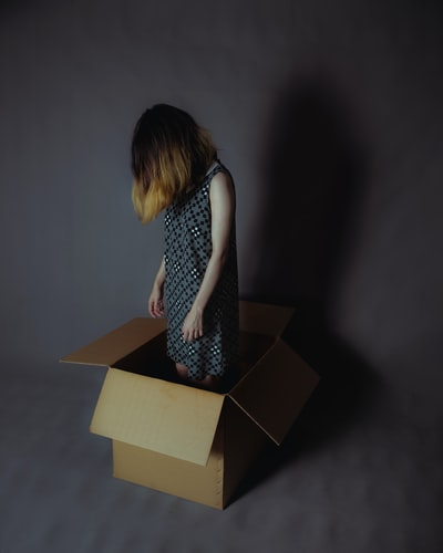 girl wearing gray and white sleeveless dress standing on cardboard box