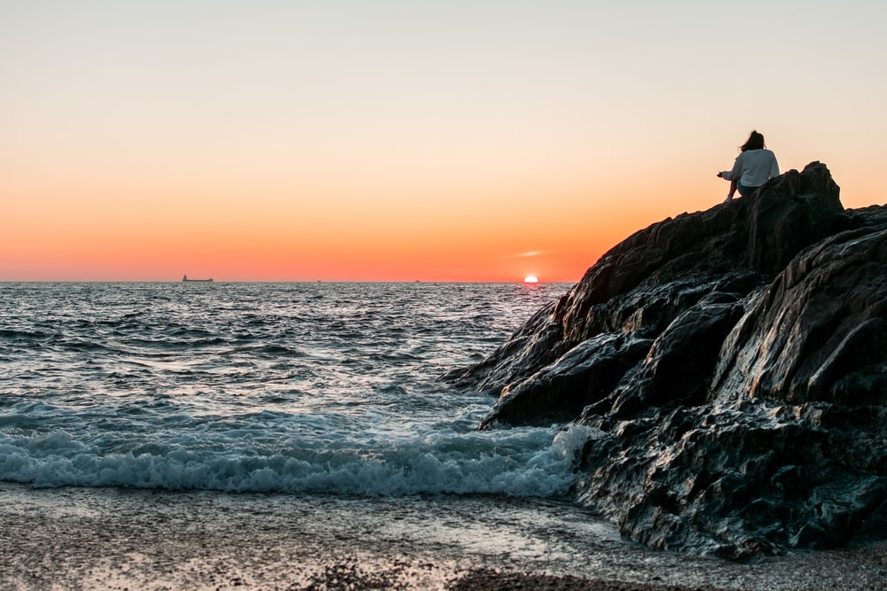person sitting on rock