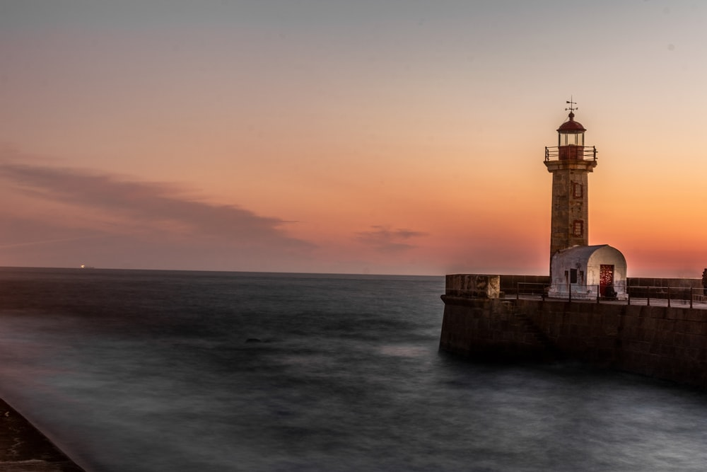 white and brown lighthouse during sunset