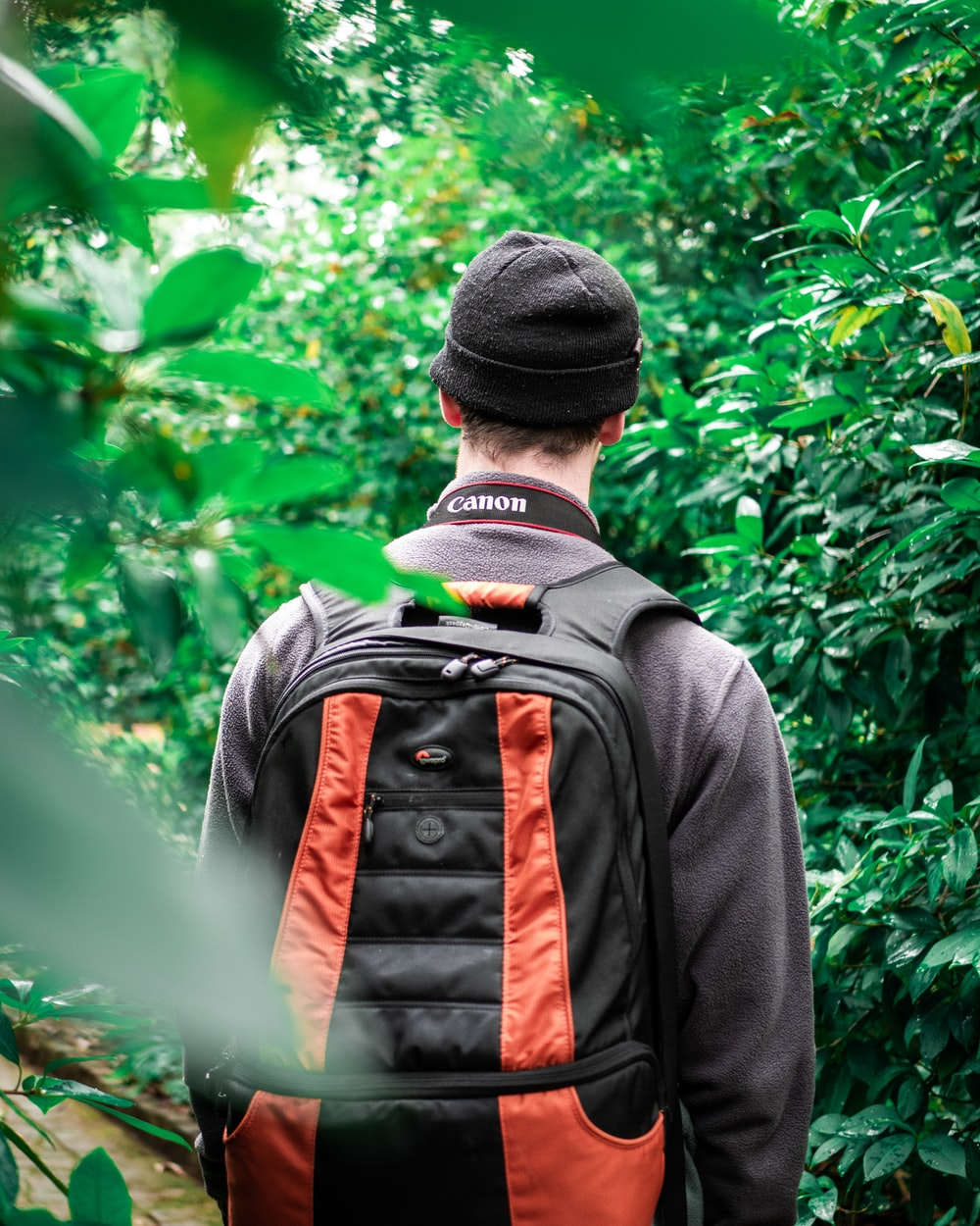 man in black jacket with backpack beside plants