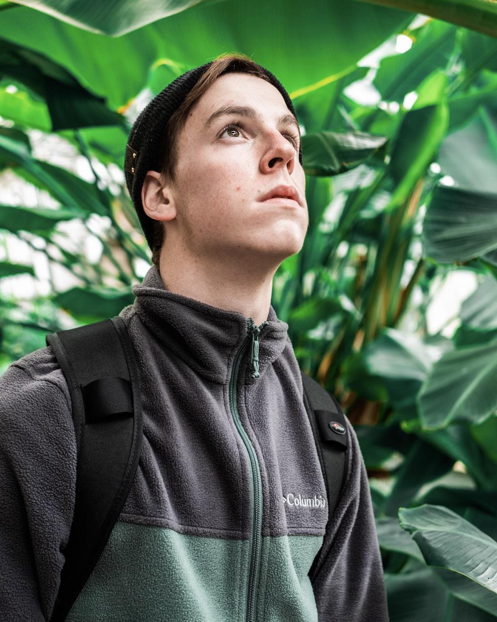 man in gray Columbia jacket beside plants