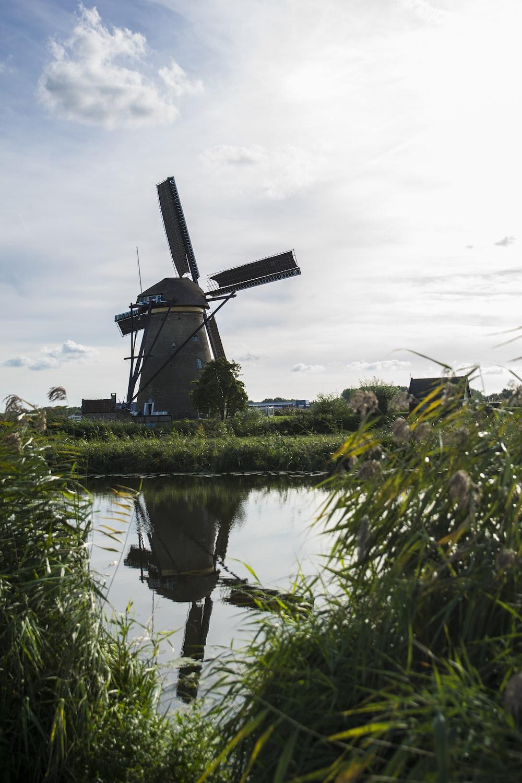 windmill beside calm body of water