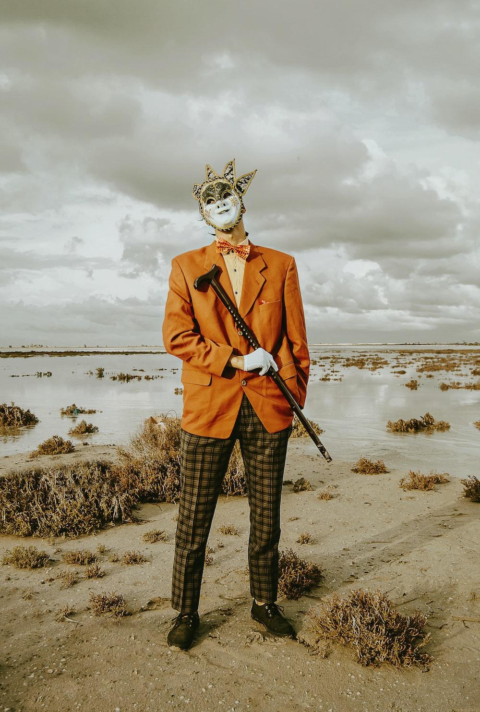 man in orange suit jacket wearing mask
