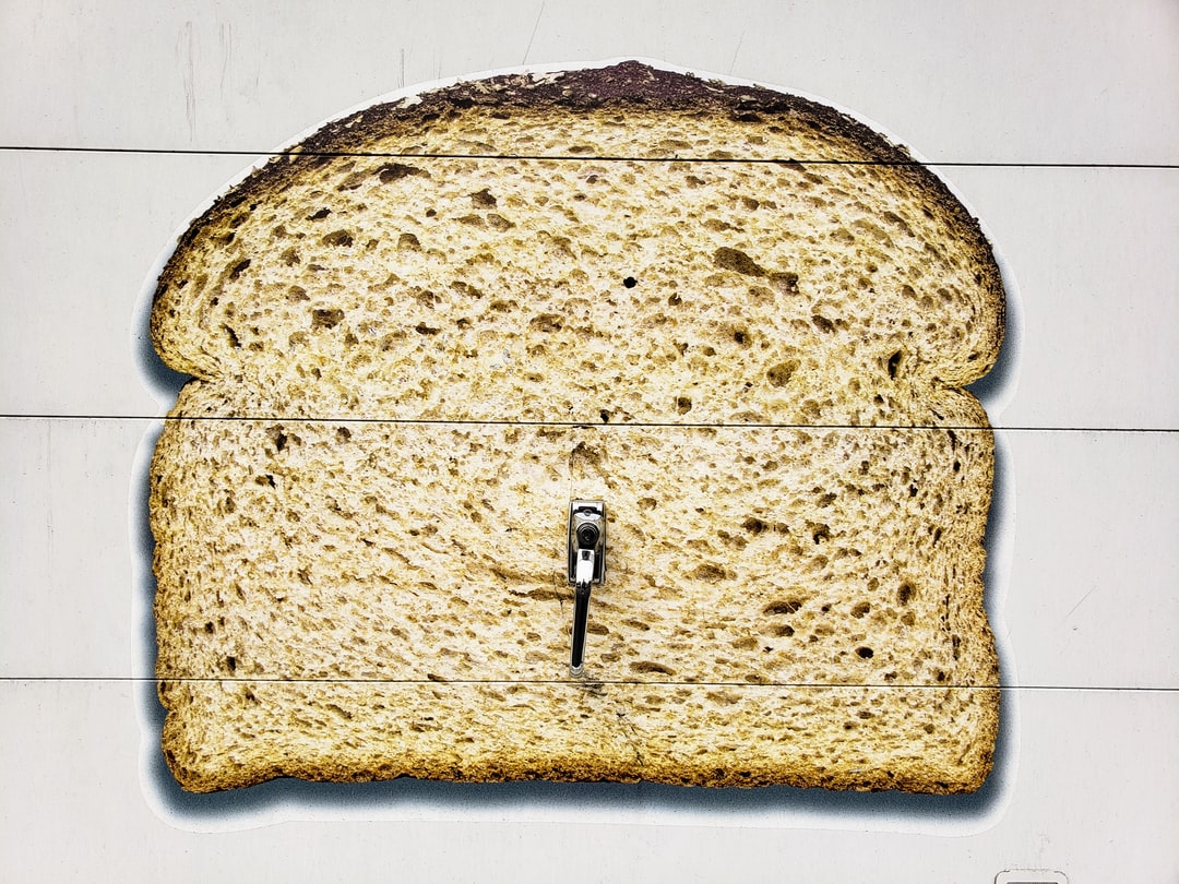 Wheat bread on white delivery truck door with lock and handle.