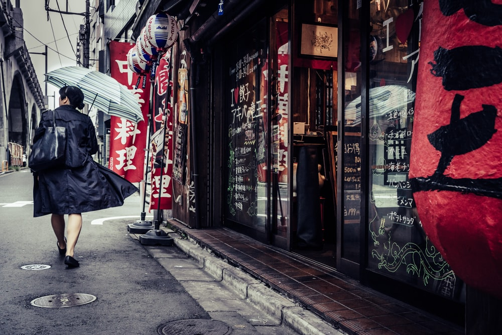 red umbrella on sidewalk near store front during daytime