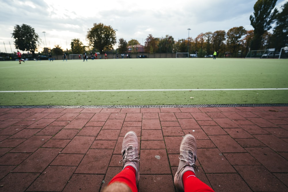 man sits in front soccer field at daytime