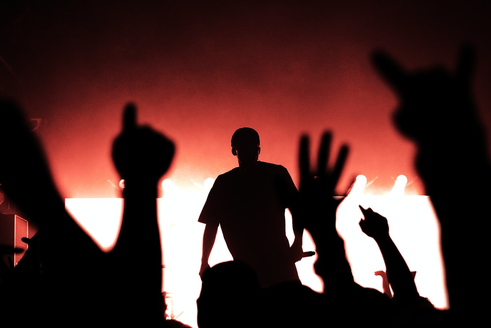 silhouette of man on stage holding microphone