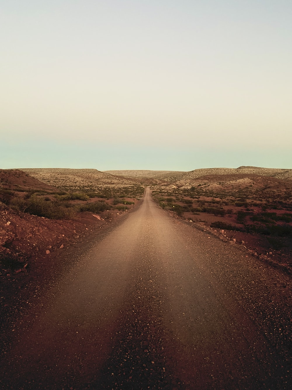 brown dirt road with mountains at distance