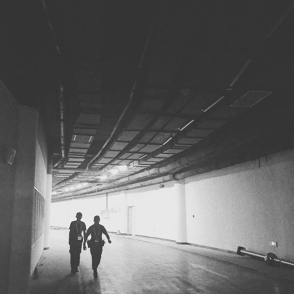 two men walks inside tunnel