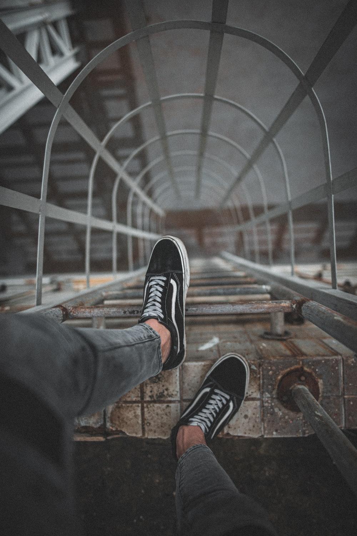 man wears black Vans low-top sneakers on top of wall ladder