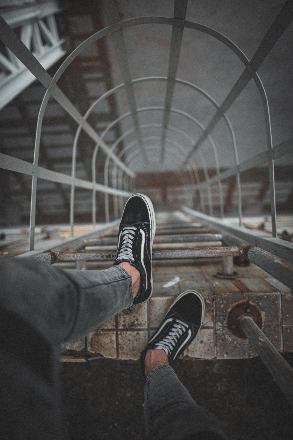 man wears black Vans low-top sneakers on top of wall ladder