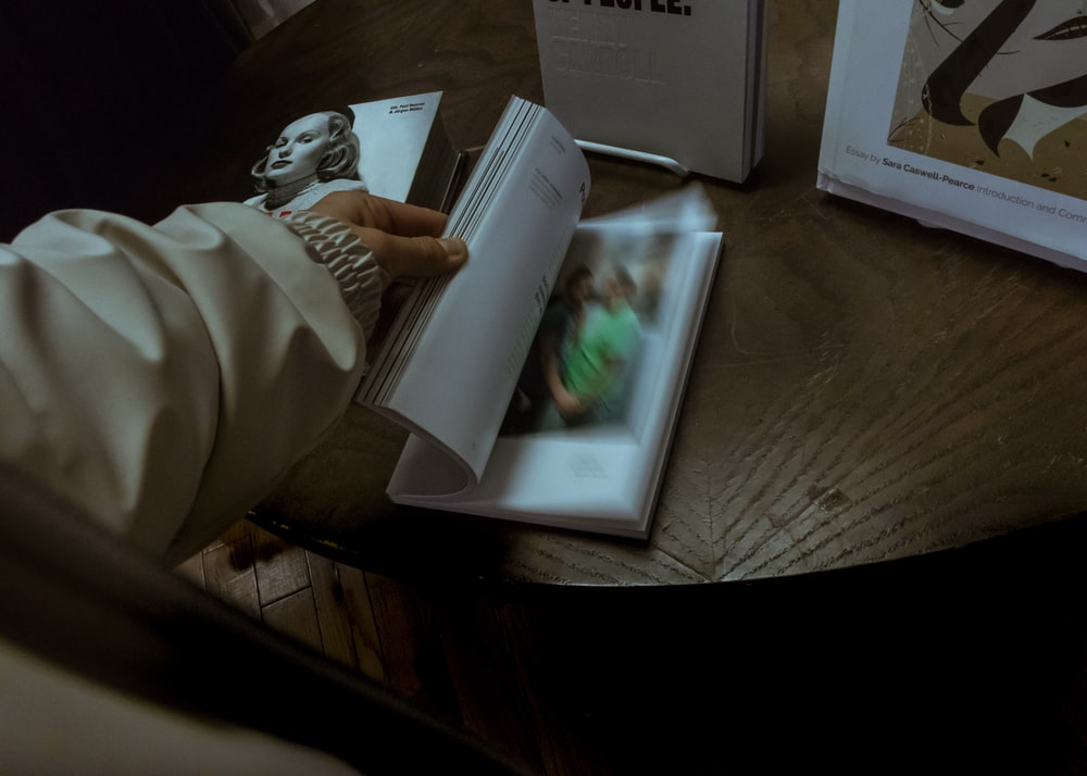 person scanning pages of a book