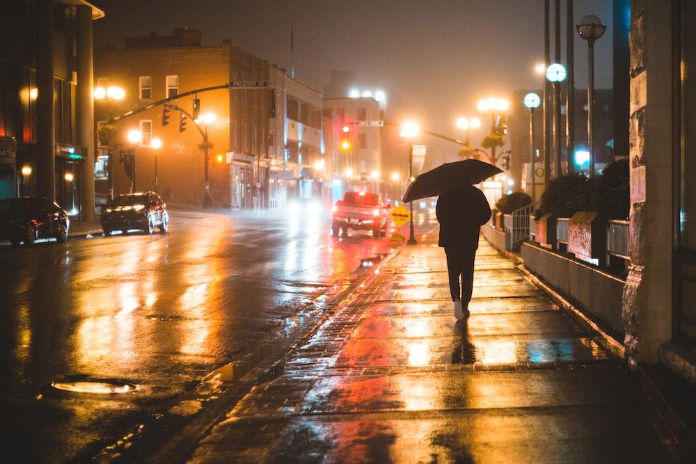 person walking on rain with umbrella